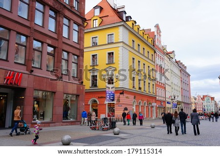 WROCLAW, POLAND - NOVEMBER 10, 2013: People passing a row of colorful buildings with stores and shops close by the old square
