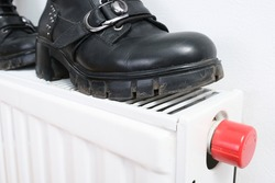 Wrong drying of footwear, a pair of dirty leather winter shoes on a hot central heating radiator.