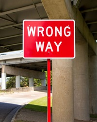 Wrong way traffic sign under a bridge