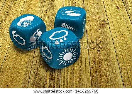 Wrong weather forecast concept poster. Inexact methods of prediction. Three dices with weather condition symbols on faces. Macro of blue gambling cubes on wooden table background #1416265760