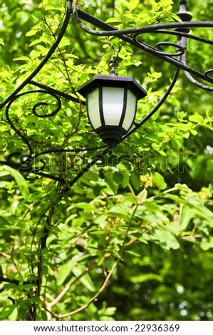 Wrought iron arbor with lantern in lush green garden - stock photo
