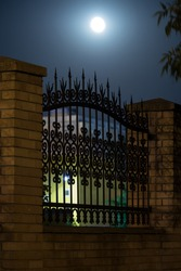 Wrought iron bars of a fence in the form of a spear in the night sky, forging and stone, wrought-iron ornaments.