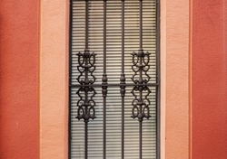 wrought iron bars on the window red wall of a house in Spain.