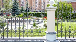 Wrought iron fence. Image of a Beautiful decorative cast iron wrought fence with artistic forging and stone columns