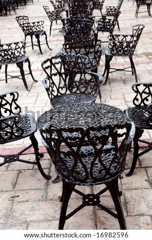Wrought iron furniture on the outdoor cafe patio - stock photo