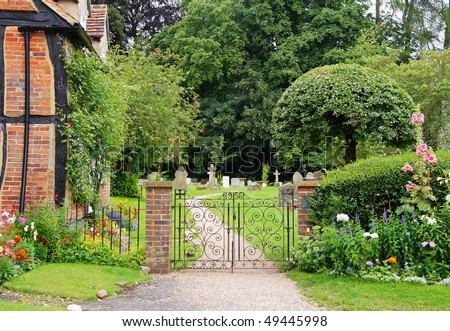 Wrought Iron Gate to an English Churchyard and Cemetery with cottage and flower filled garden