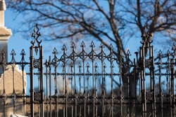 Wrought iron gothic fences surrounding an old cemetary with dead trees