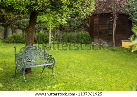 Wrought Iron Steel Patina Bench in Manicured Garden Courtyard
