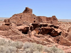 Wupatki National Monument and the Wupatki (tall house) pueblo. The dwelling's walls were constructed from thin, flat blocks of the local Moenkopi sandstone, giving the pueblo its distinct red color.