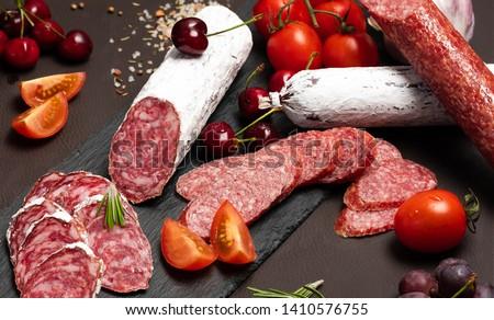 Wurst, Fuet, Sausage sliced on black background. Delicatessen. Сток-фото ©