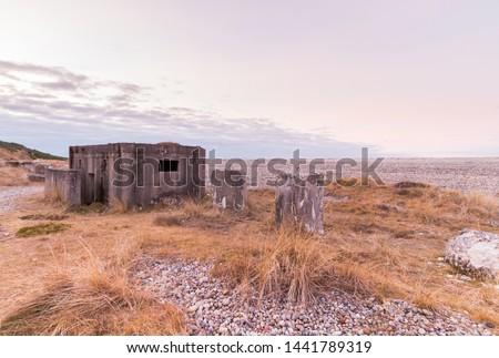 WW2 coastal beach defences with concrete anti tank blocks and a pillbox #1441789319