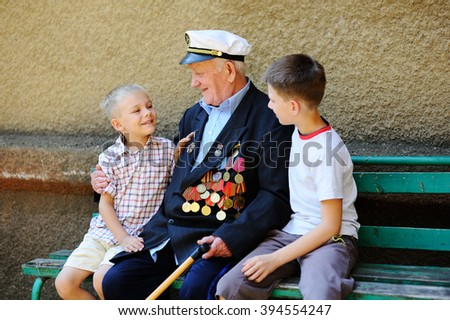 WWII veteran with children. Grandchildren looking at grandfather\'s military awards.
