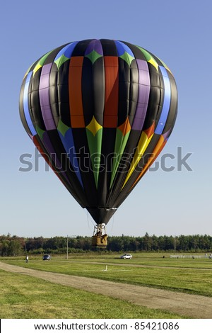 X Marks the Spot.  Colorful hot air balloon dips low to ground to drop beanbag directly on target.