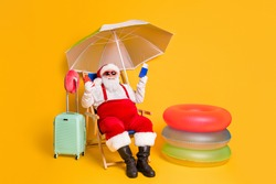 X-mas online tickets resort buy. Full body photo of white grey hair bearded santa claus sit chaise-lounge hold smart phone passport wear red sunglass cap isolated yellow color background