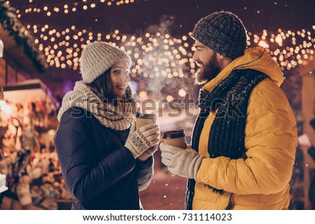 X mas time! Cute married family is having a walk in park on a cold night, enjoying tea, dressed warm in head wear, gloves, scarves, looking at each other, chatting, laughing
