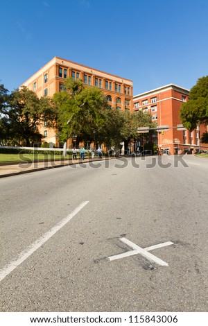 X on the road where President John F. Kennedy was assassinated with the Book Depository in the background