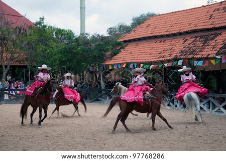 XCARET, MEXICO - MARCH 6: An Xcaret Rodeo show performer displaying her horse riding skills on March 6, 2012 in Xcaret, Mexico. The Xcaret park is a major tourist attraction in the area.