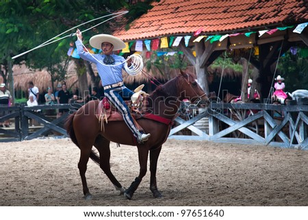 XCARET, MEXICO - MARCH 6:  An Xcaret Rodeo show performer displaying his lasso handling skills on March 6, 2012 in Xcaret, Mexico. The Xcaret park is a major tourist attraction in the area.