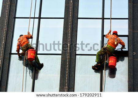 XIAMEN, CHINA - JANUARY 12: As a dangerous work, external wall cleaner is working on a building in Xiamen, Fujian Province, China in January 12, 2014. Xiamen is a developing city located in South of China.