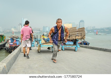 XIAMEN - JULY 7: harbor workers transport goods at Gulangyu harbor on July 7, 2013 in Xiamen, China. Although Xiamen is China\'s no.8 biggest harbor there is still a lot of physical labor activity.