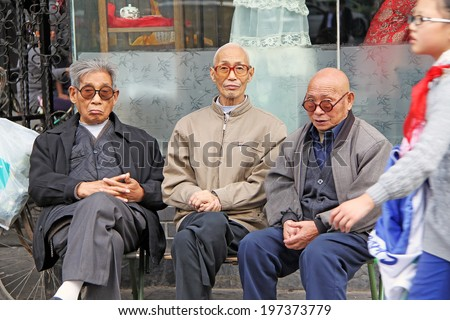 XIAN, CHINA - OCTOBER 13, 2009: elderly men and young pioneer on the one of the main streets of Xian city,China on October 13,2009. China pioneers consist of children between ages of six and fourteen.