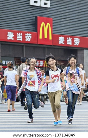 XIANG YANG-CHINA-JULY 3, 2012. Teenagers in front of McDonald's on July 3, 2012 in Xiang Yang. It took McDonald's 19 years to reach 1,000 restaurants in China. It plans to raise it to 2,000 by 2013.