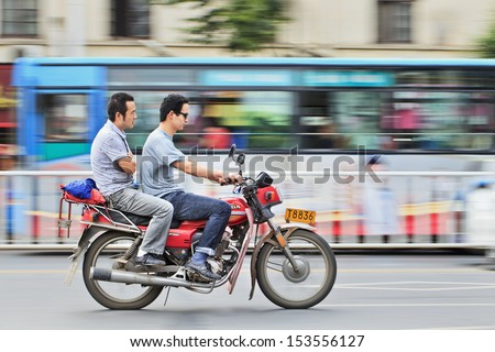 XIANG YANG-CHINA-JULY 1. Two men on a gas motorcycle. Demand for gas motorcycles in China increases primarily in rural areas because of urban bans and restrictions. Xiang Yang, July 1, 2012.