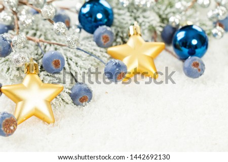 Xmas background. Green Xmas tree twig, gold stars, frozen berries and Christmas decoration on white snow #1442692130