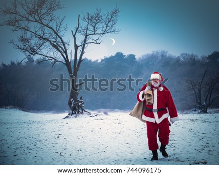 Xmas, cold, December. Santa Claus going with a bag of gifts in the winter on snow-covered field.