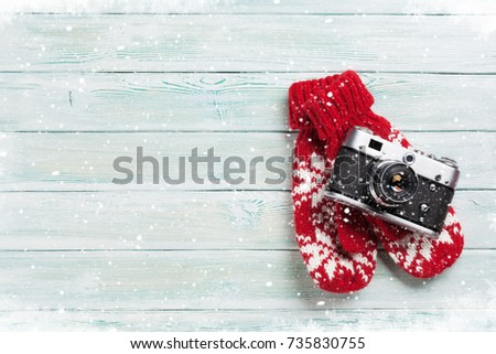 Xmas greeting card. Christmas background with camera and mittens. View from above with space for your greetings or photo #735830755