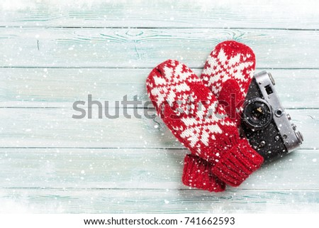 Xmas greeting card. Christmas background with camera and mittens. View from above with space for your greetings or photo #741662593