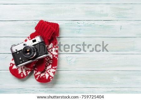 Xmas greeting card. Christmas background with camera and mittens. View from above with space for your greetings or photo #759725404