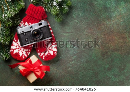 Xmas greeting card. Christmas background with snow fir tree, camera and gift box. View from above with space for your greetings or photo #764841826