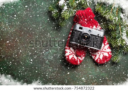 Xmas greeting card. Christmas background with snow fir tree, camera and mittens. View from above with space for your greetings or photo #754872322