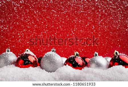 Xmas greeting card design and background. Red and silver baubles in snow on red backdrop, copy space #1180651933