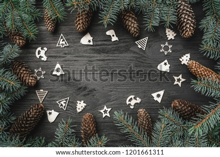 Xmas greeting card. Text space, intro frame of fir branches and cones. Christmas wooden toys. Top view #1201661311