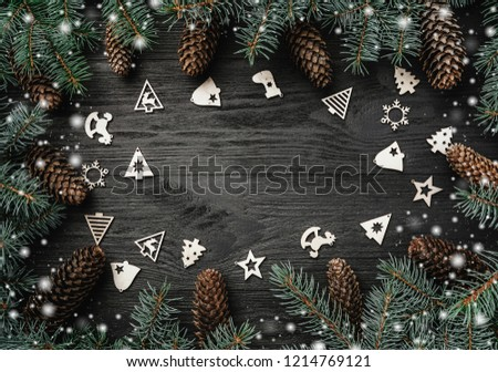 Xmas greeting card with snow effect. Text space, intro frame of fir branches and cones. Christmas wooden toys. Top view #1214769121