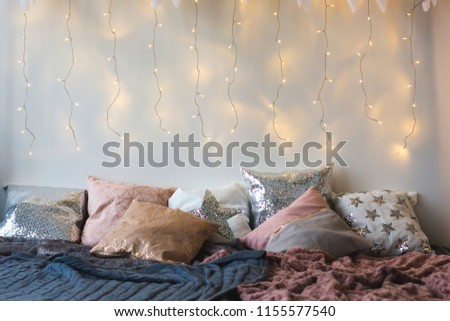 Xmas in morning bedroom. Double bed In christmas Interior on white wall background with cozy lights. Gift box on bed. Many pillows on bed