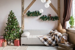 Xmas in morning living room. Sofa bed In christmas Interior. celebrate the new year and holidays. Christmas tree and gingerbread house