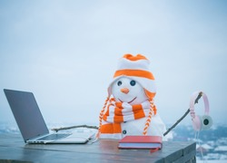 Xmas or christmas decoration, audio book. Happy holiday celebration, new technology. New year snowman in hat. Christmas and education, fairytale. Snowman in winter with laptop, headset and book.