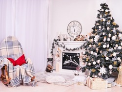 Xmas Tree and Fireplace with armchair, gifts, clocks and pillows. Christmas stocking over fireplace, New Year's card scenery. Snowman and stars. New Year concept