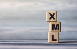 XML (eXtensible Markup Language) - word on wooden cubes against the background of a light board with beautiful divorces. Business and Technology concept.