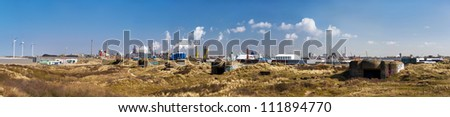 XXL panorama of the dunes of Ijmuiden with old ww2 bunkers in the front and heavy industry in the background - stock photo