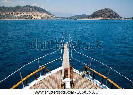 Yacht at sea with the mountains in the background - stock photo