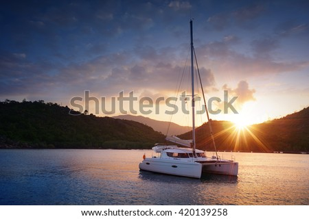 Yacht - Catamaran in the tropical sea at sunset. Yachting theme. Yachting background. Sailing time. Sailboat. Yacht. Luxury yacht.