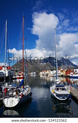 Yacht in picturesque harbor of Henningsvaer on Lofoten islands in Norway