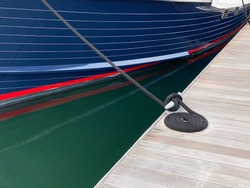 Yacht in port with nautical rope coiled on wooden dock