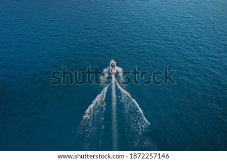 Yacht in the rays of the sun on blue water.  Drone view of a boat  the blue clear waters.  Top view of a white boat sailing to the blue sea.  Aerial view luxury motor boat. stock photo