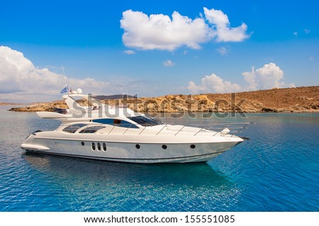 Yacht In The Sea Around The Island On A Background Of The Sky With Clouds