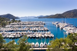 Yacht Marina. Footage of many luxury boats and yachts in the harbor. Beautiful forested mountain landscape in the background. Gocek Marina, Mediterranean coast, Fethiye TURKEY